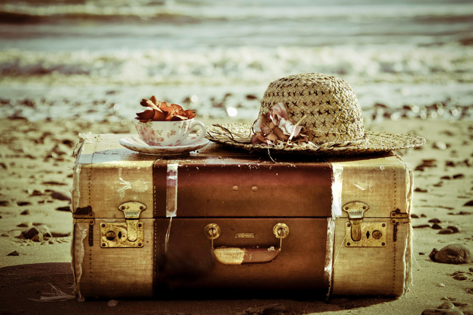 old-suitcase-hat-tea-cup-on-a-beach